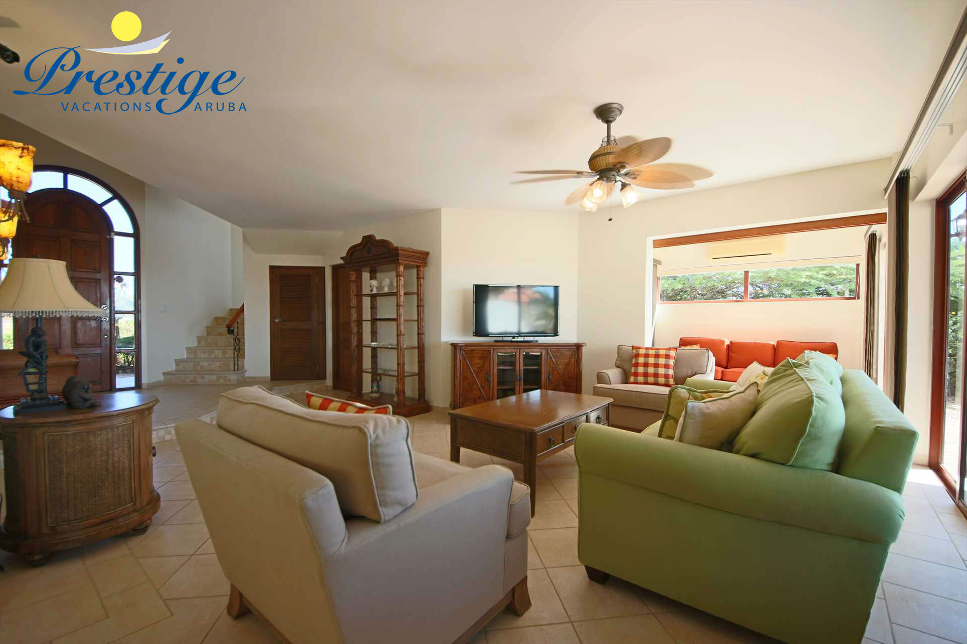 The living area with a 3-seat sofa set plus chairs and a large TV