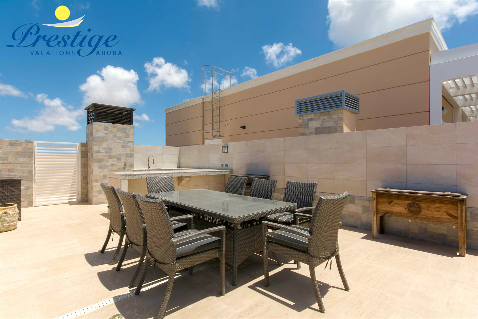Outdoor kitchen with a sink, cooking plate, a wine fridge, and outdoor dining table