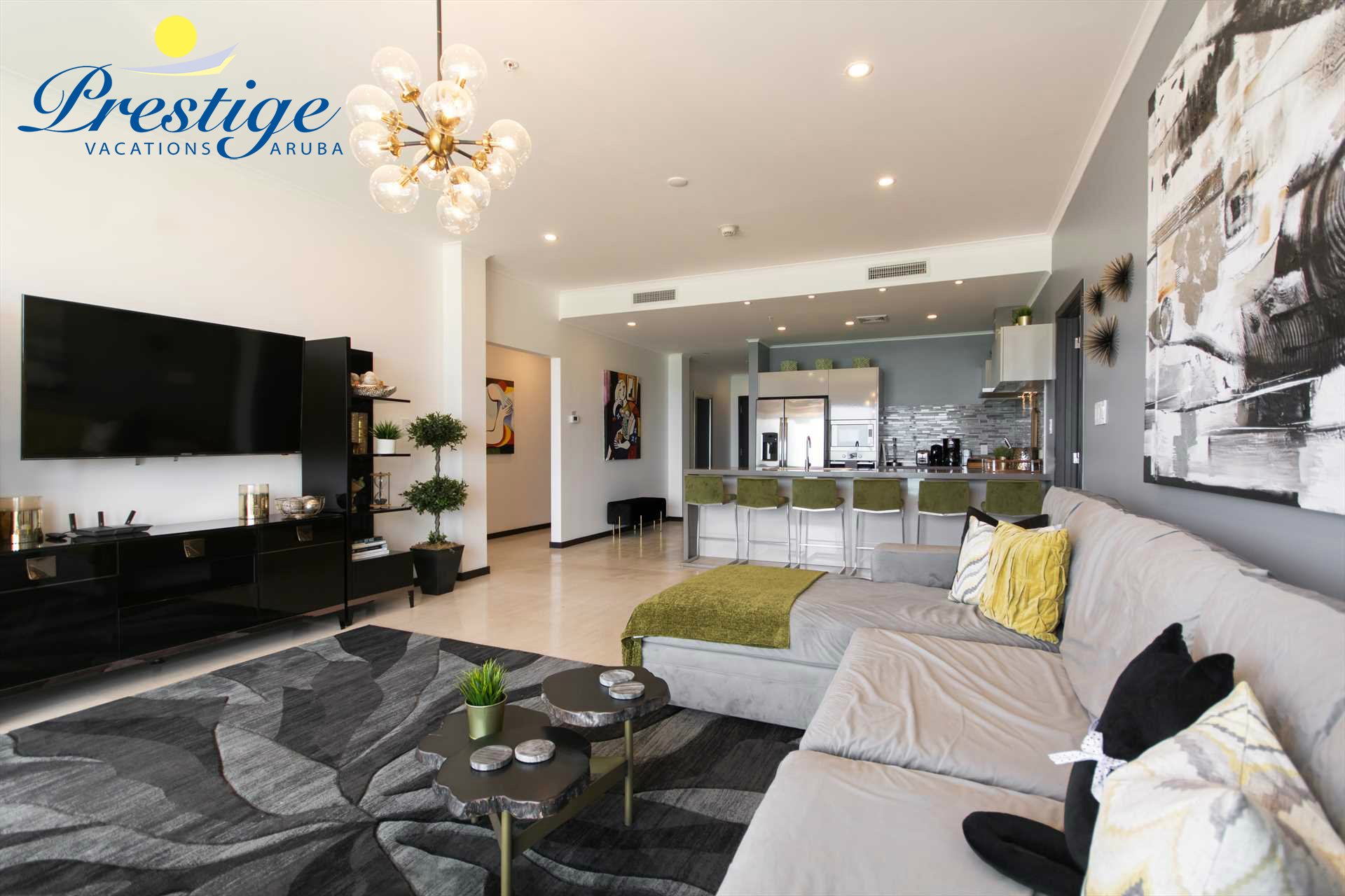 The spacious living area with a large TV and a large sofa with a chaise
