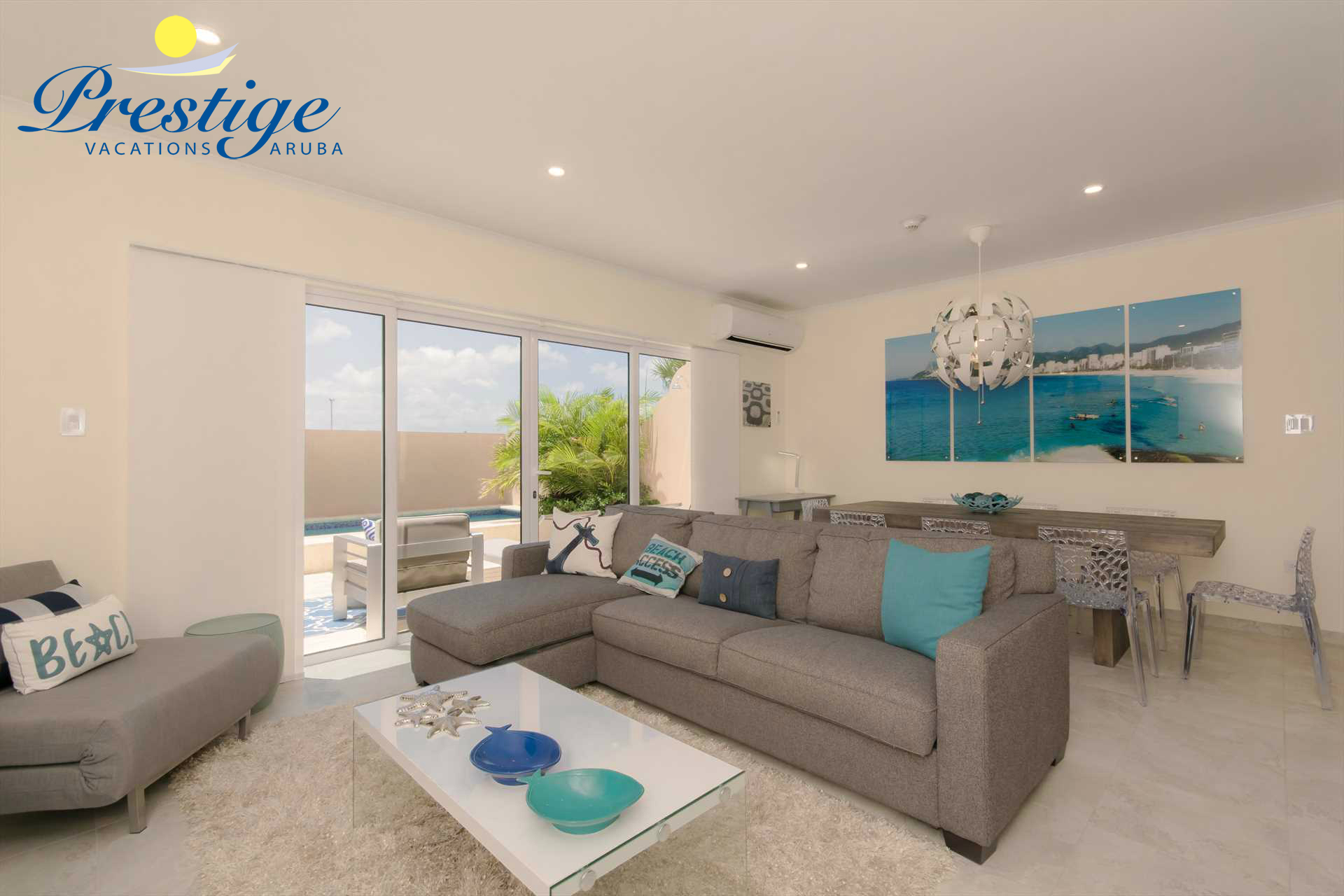 Living area with with 3-seat sofa-bed plus a large TV and a large Ipanema Beach wall art