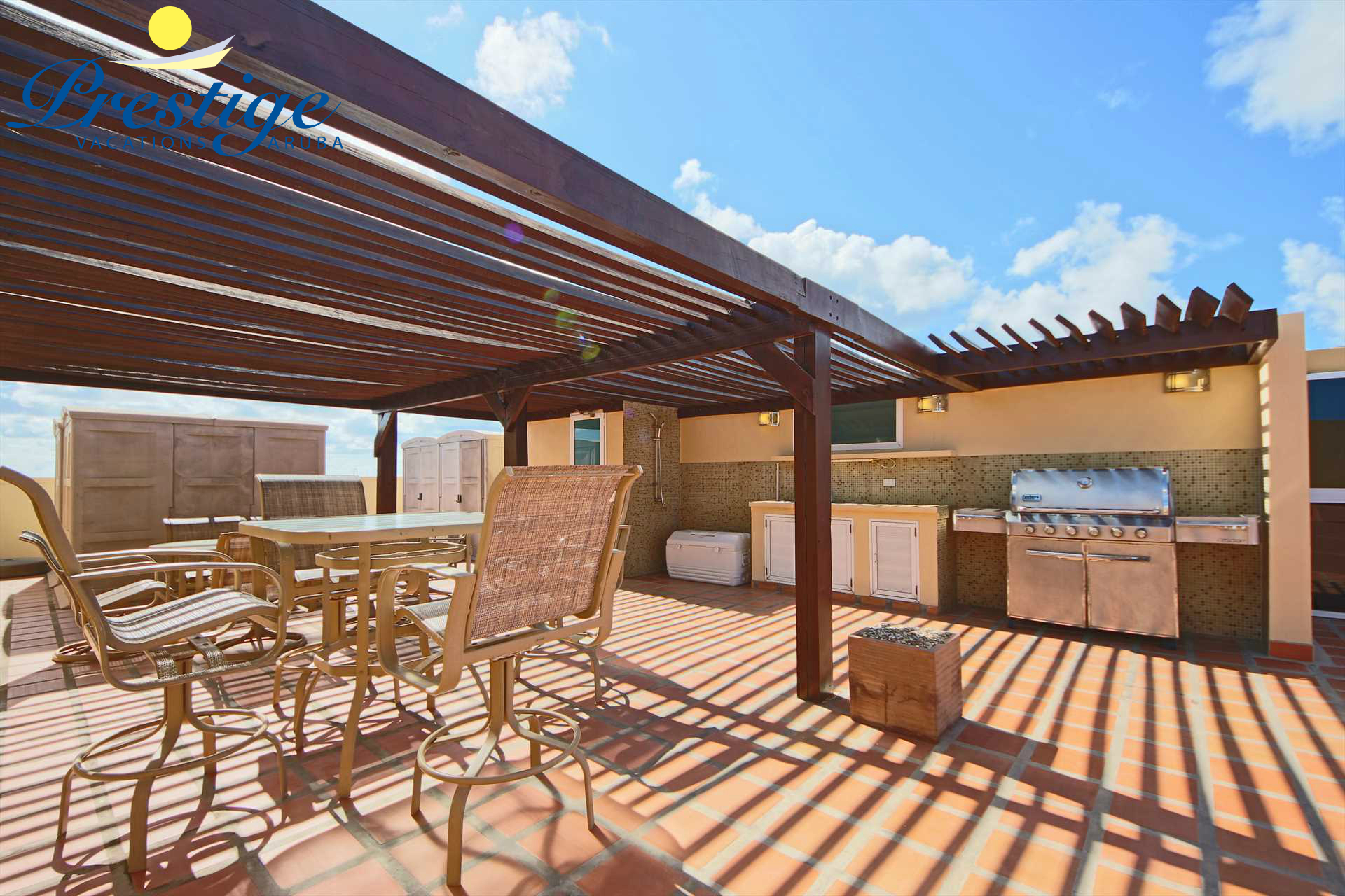 Semi covered rooftop with outdoor kitchen with a sink and large BBQ-grill