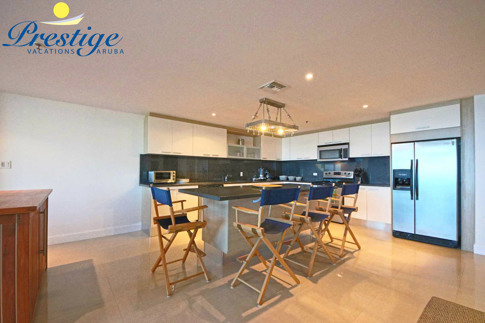 The fully equipped kitchen with 4-bar stools around the large kitchen island