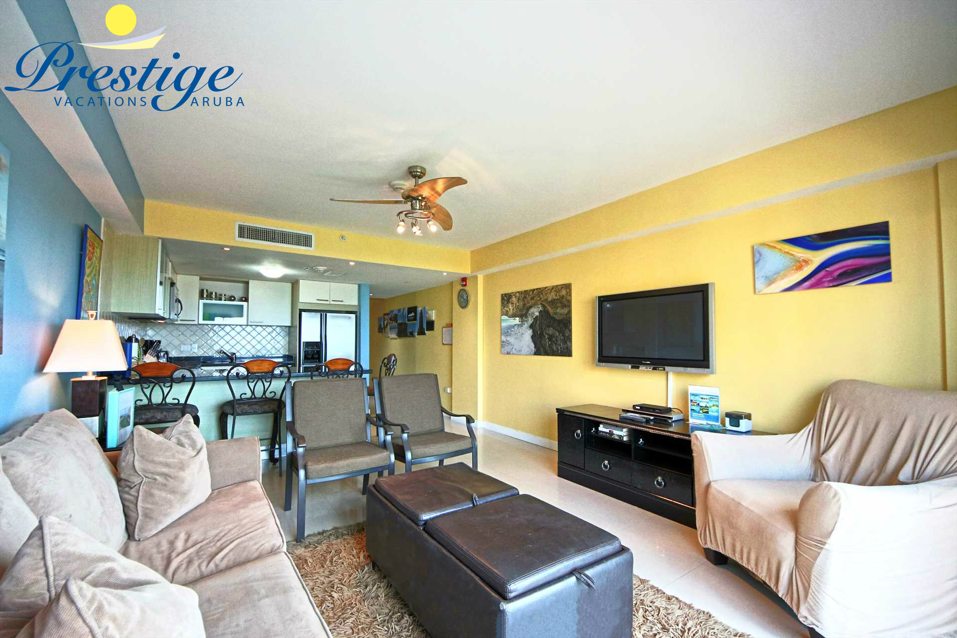 Another full view of the living room with beautiful local art and Aruba scenery photographs