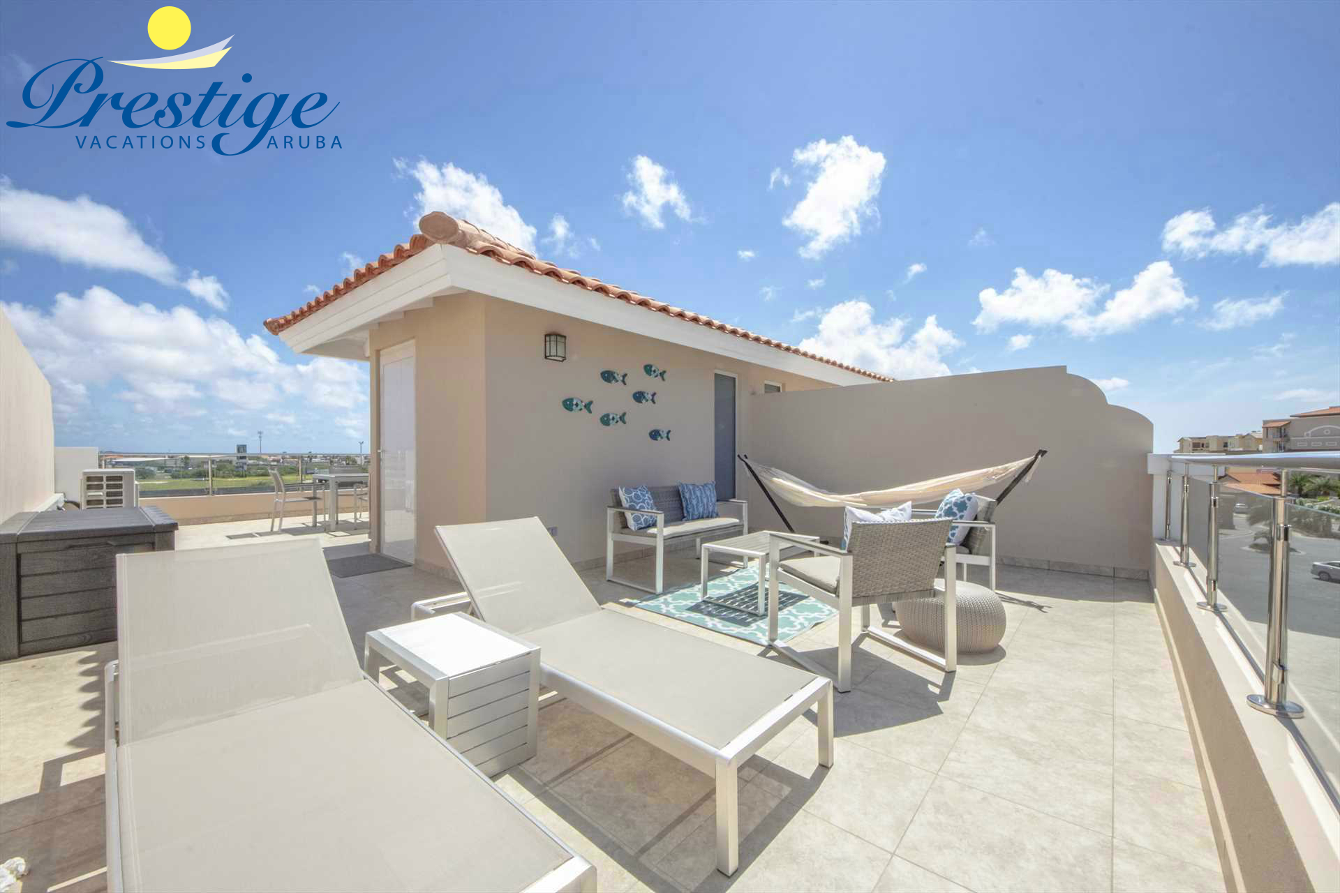Private rooftop terrace with an outdoor seating area, chaise lounges and hammock