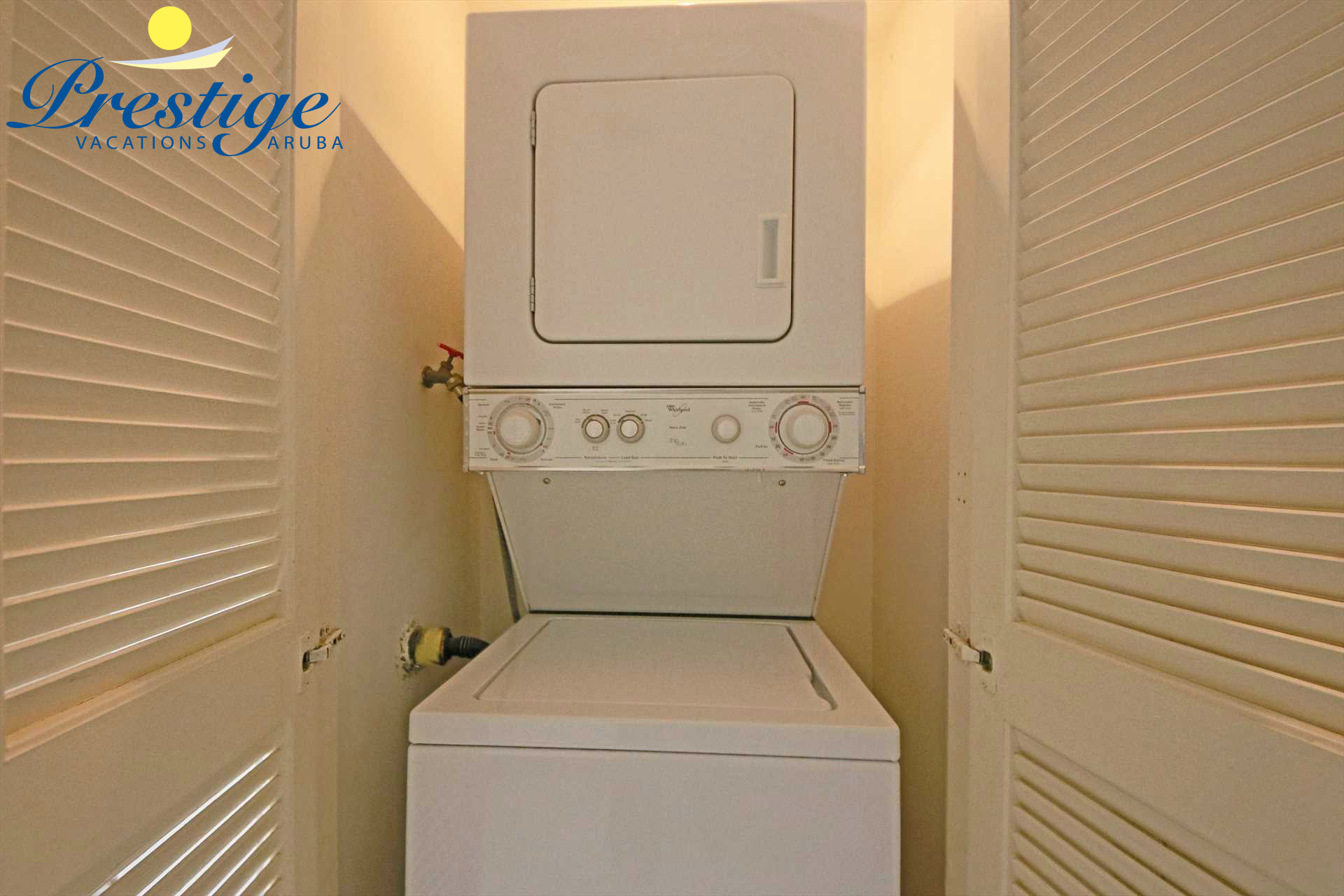 the laundry closet with stacked washer/dryer combo