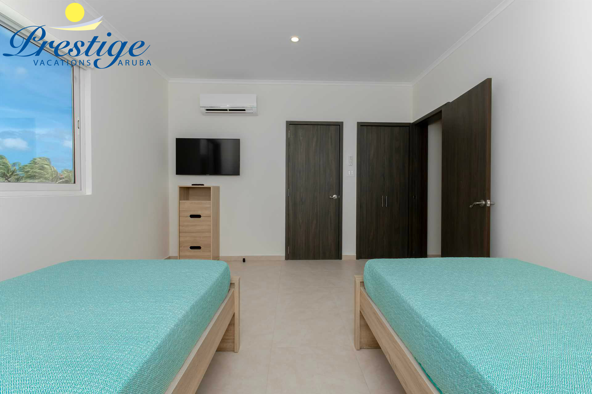 The second bedroom with a TV, walk-in closet and en-suite bathroom