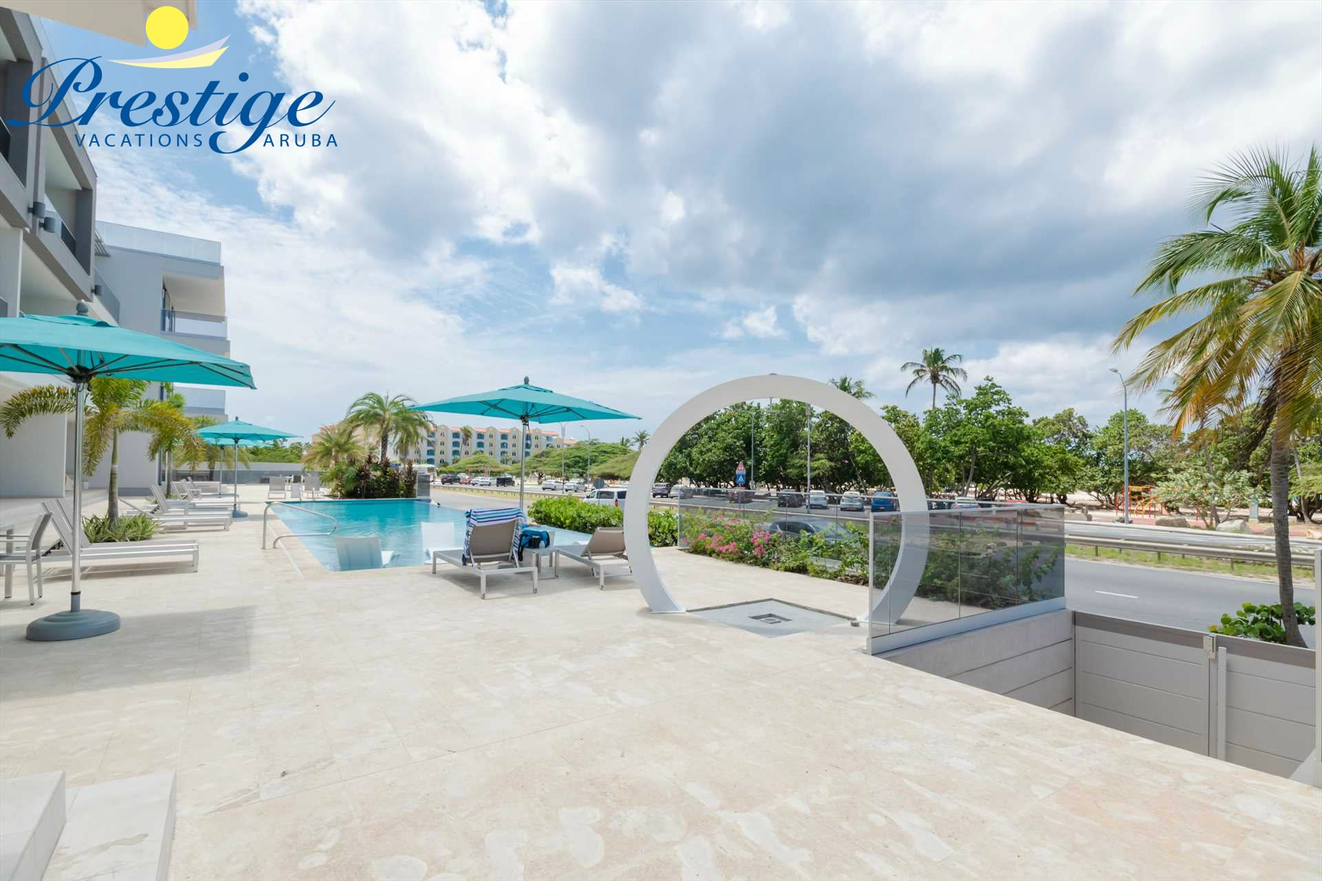 The resort beachfront pool area with infinity-edge swimming pool, a stunning O-shaped outdoor shower, and a beach access gate