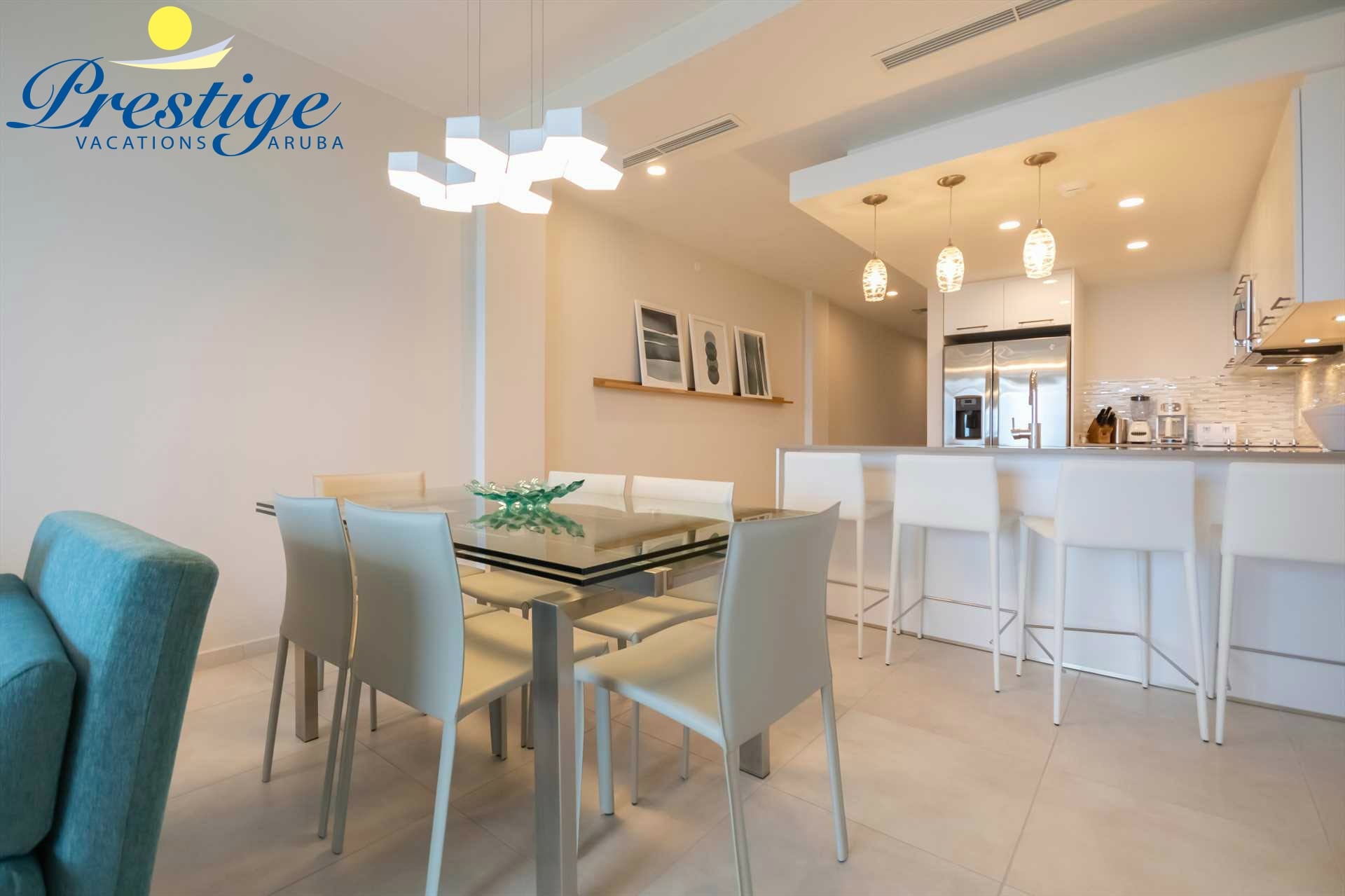 Living area with a 6-seat dining table and the kitchen